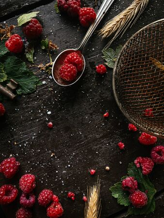Top view on home grown raspberries on a dark wooden table background with clear copy space for text for a homemade recipe