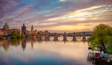 Charles Bridge during beautiful romantic colorful spring summer golden hour before sunset with wonderful blue sky with clouds