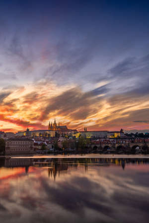 View on Charles Bridge and Prague Castle over Vltava River during early night with wonderful dusk sunset sky