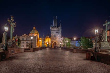 Empty Charles Bridge in the center of Prague during first wave of Covid-19 pandemy in the night with blue sky and yellow lights Banco de Imagens - 161619314