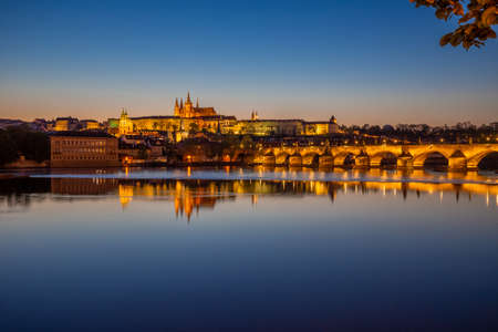 View on Charles Bridge and Prague Castle over Vltava River during early night with wonderful blue sky and yellow city lights