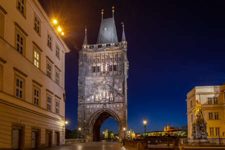 Empty Charles Bridge in the center of Prague during first wave of Covid-19 pandemy in the night with blue sky and yellow lights