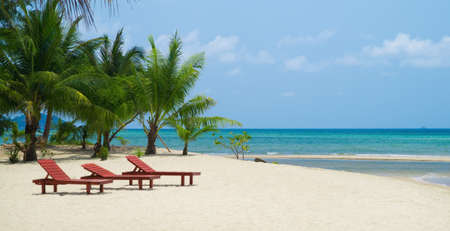 Three red wooden beach chairs on white sand against blue ocean with coconat palm trees  background.  photo