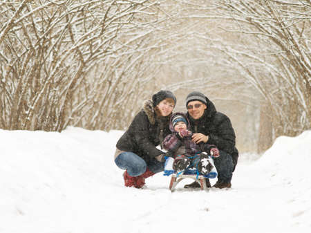 Young couple outdoors with son on the sled photo