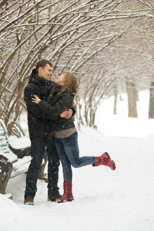 winter couple: Young couple outdoors giving each other a hug