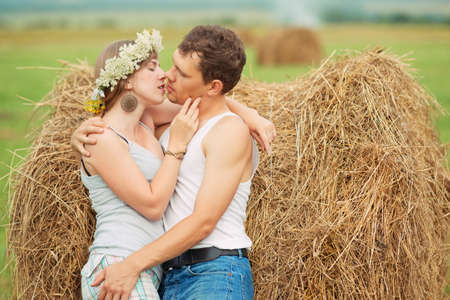 cute young farm girl: romantic couple kissing near haystack