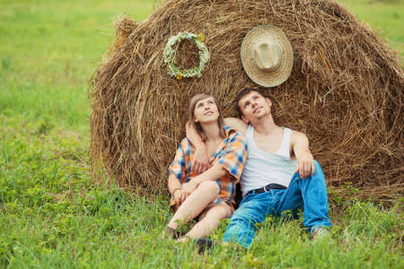 romantic couple sitting on a grass near haystack photo