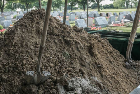 grave: Cemetery Grave Dirt Pile and Shovels. A pile of fresh dirt and shovels in a cemetery. Grave ready for a funeral.