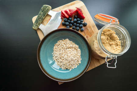 oatmeal: Oatmeal Breakfast and Fruit. Dry oatmeal, berries and brown sugar with cooking utensils on a brown cutting board.