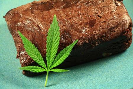 hoja marihuana: Pot Brownie 3. Una hoja de marihuana en un brownie de marihuana en una placa azul. Foto de archivo