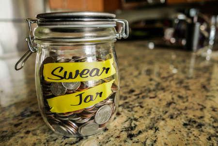 """frasco: Swear Jar. Un frasco de vidrio transparente presentó con monedas y billetes, el ahorro de dinero. Las palabras """"Swear Jar"""", escrita en el exterior."""