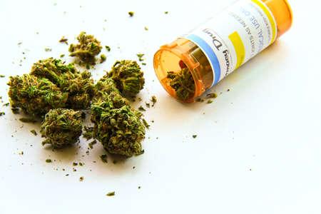 recetas medicas: Marihuana Medicinal A. La marihuana medicinal derramamiento de una botella de prescripción en contra de blancos. La etiqueta de la botella es original, por lo que no hay cuestiones de marcas o derechos de autor