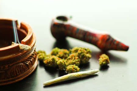 foreground focus: Marijuana Joint and Pipe 2. Marijuana Joint and Pipe laying on a shiny black wooden surface. Focus on the foreground.