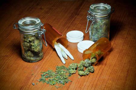 marihuana: Marihuana En la Tabla. La marihuana en una mesa de madera. En pilotes, jarras, botellas de prescripción y rodado en las articulaciones.