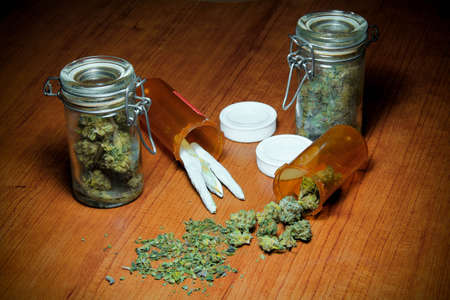 medicinal marijuana: Marijuana On Table. Marijuana on a wood table. In piles, jars, prescription bottles and rolled into joints.