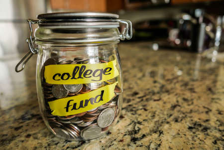 money jar: College Fund Money Jar. A clear glass jar filed with coins and bills, saving money. The words College Fund written on the outside. Stock Photo
