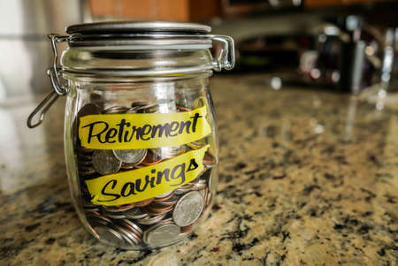 retirement savings: Retirement Savings Money Jar. A clear glass jar filed with coins and bills, saving money. The words Retirement Savings written on the outside. Stock Photo