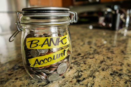 save: Bank Account Money Jar. A clear glass jar filed with coins and bills, saving money. The words Bank Account written on the outside.