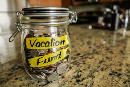 vacation: Vacation Fund Money Jar. A clear glass jar filed with coins and bills, saving money. The words Vacation Fund written on the outside. Stock Photo