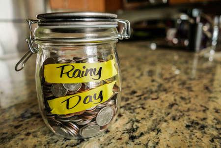 """fondos negocios: Tarro del día lluvioso dinero. Un frasco de vidrio transparente presentó con monedas y billetes, el ahorro de dinero. Las palabras """"Rainy Day"""", escrita en el exterior."""