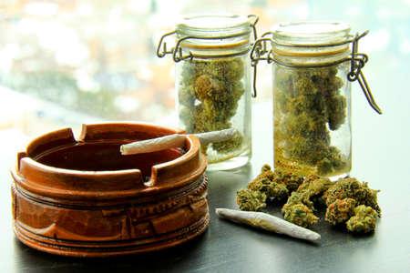 marihuana: Marihuana Articulaciones y Jars of Weed. Un cigarrillo de marihuana en un cenicero, con otro conjunto, una pila y dos frascos llenos de más marihuana.