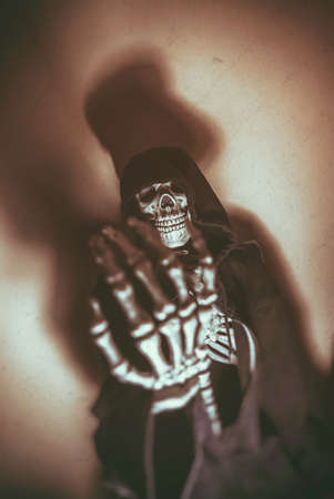 reaching out: Dark Skeleton Hand Blur Skull. Skeleton in hoodie with hand reaching out as if begging or reaching for viewer. Shot with spot lighting and edited with vintage filters. Hand blurred, skull in focus.