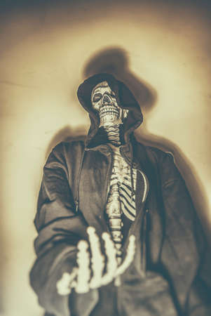 reaching out: Skeleton Beggar. Skeleton in hoodie with hand reaching out as if begging. Shot with spot lighting and edited with vintage filters.