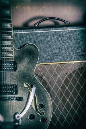 gitara: Gitara i wzmacniacz vintage Bliska. Gitara i wzmacniacz, strzał z oświetlenia punktowego i edytowane z rocznika filtra. Zdjęcie Seryjne