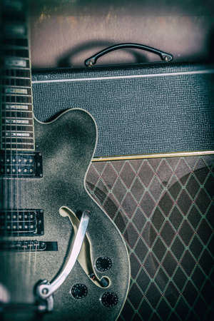 amp: Guitar and Amplifier Vintage Close Up. Guitar and amplifier, shot with spot lighting and edited with a vintage filter. Stock Photo