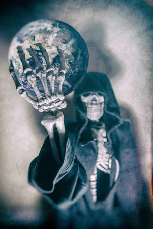 holding up: Grim Reaper Holding the Earth. Grim Reaper in hood holding up the Earth. Shot with spot lighting and edited with vintage filters.