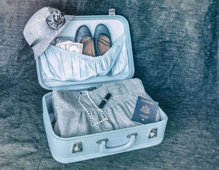 voyage vintage: Vintage Travel Suitcase. Open vintage suitcase ready for travel. Containing hat, shoes, dress, pearls, lipstick and passport.