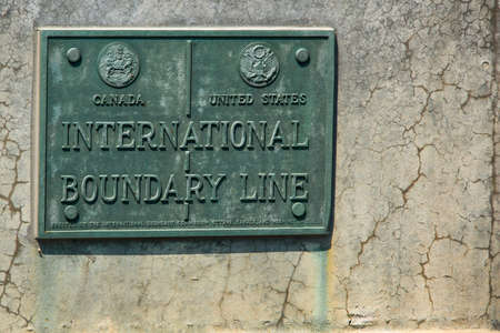 state boundary: International Boundary Line Canada USA. Plaque indicating the international boundary line between the United States and Canada. On the QueenstonLewiston bridge, New York state and the province of Ontario. Editorial