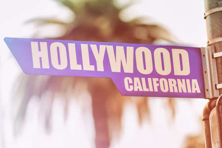 Hollywood California Street Sign. A street sign marking world famous Hollywood, California. Backed by a palm tree with a sunset flare.