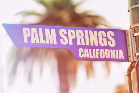 Palm Springs California Street Sign. A street sign marking Palm Springs, California. Backed by a palm tree with a sunset flare. Stock Photo