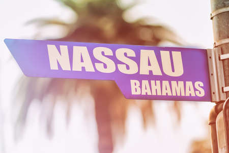 Nassau Bahamas Street Sign. A street sign marking Nassau, Bahamas. Backed by a palm tree with a sunset flare.