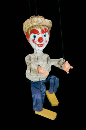 Mexican Marionette Puppet. A cheap hand-made marionette puppet from Mexico on black. Stock Photo