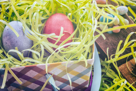 soft colors: Easter Eggs Pair in Basket. Holiday Easter eggs and grass with soft pastels colors and lighting. Some vintage filters added.