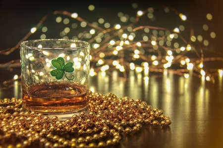 saint patty's: Irish Whiskey St Patricks Clover. Irish whiskey in a glass with a clover symbol, on a pub table with gold beads and bar lights. Stock Photo