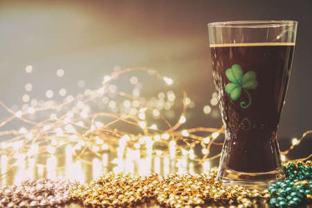 saint patty's: St Patricks Day Irish Stout Beer. Traditional Irish stout, a dark beer. On a pub bar rail table with lights and St Patricks Day party beads. Stock Photo