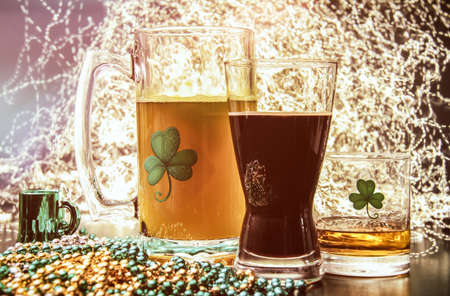 St Patricks Day Pub Alcohol. Saint Patricks Day pub items, including a large mug of beer, a glass of Irish stout, and a shot of Irish Whiskey neat. Set against a celebration lit background.