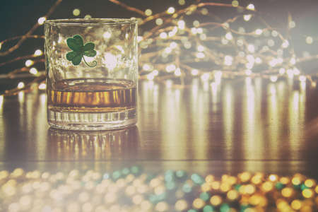 saint patty's: Irish Whiskey St Patricks Clover Golden Glow. Irish whiskey in a glass with a clover symbol, on a pub table with gold beads and bar lights.