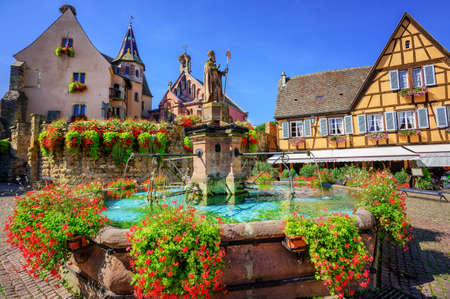 Half-timbered medieval houses decorated with flowers in Eguisheim village along the wine route in Alsace, France