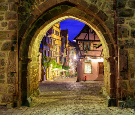 old city: View of Riquewihr, Alsace, France, through city wall gate at night Stock Photo