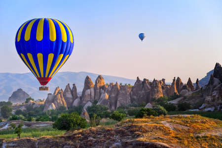 Cappadocia hot air balloon flying over bizarre rock landscape in Turkey Redakční