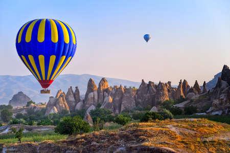 country landscape: Cappadocia hot air balloon flying over bizarre rock landscape in Turkey Editorial