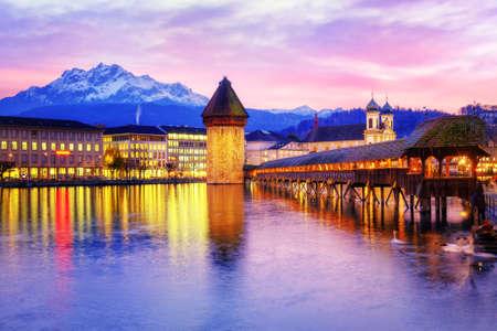 lucerne: Chapel bridge, Water tower and Mount Pilatus on sunset, Lucerne, Switzerland. Stock Photo