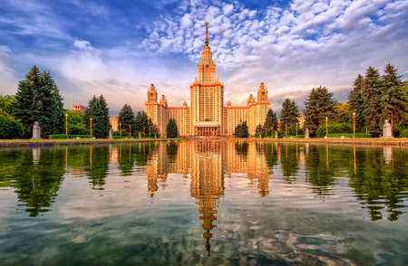 neoclassical: Neoclassical Moscow State University MGU building on Vorobyevy Gory, reflecting in lake, Russia Stock Photo