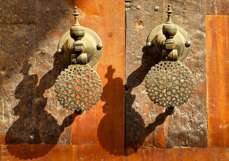 door knobs: Decorated ornamental bronze door knobs the gates of moroccan palace in evening sun Stock Photo