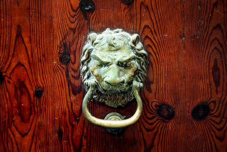 door lock: Decorative bronze lion head door knob on a dark wooden background Stock Photo