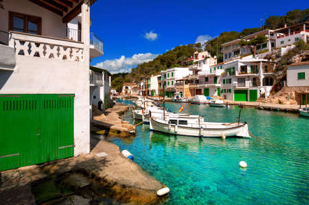 majorca: White villas and boats on green water in picturesque fishermen village Cala Figuera, Mediterranean Sea, Mallorca, Spain